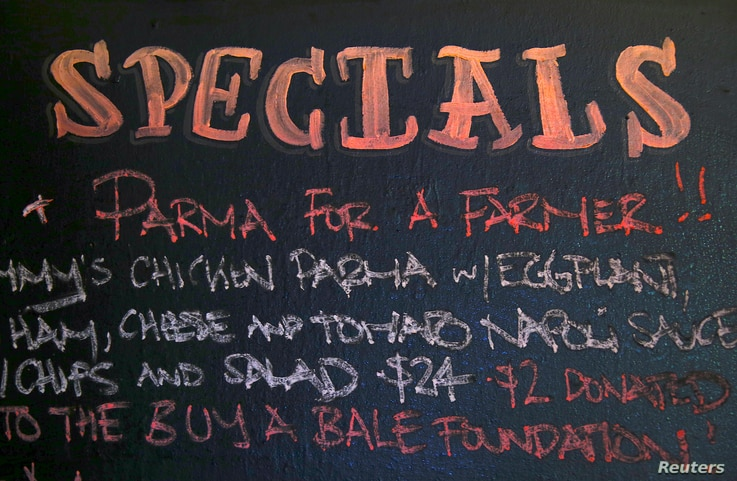 A menu board at Sydney's Old Fitzroy Hotel displays the slogan 'Parma for a Farmer', meaning that sales of the dish will result
