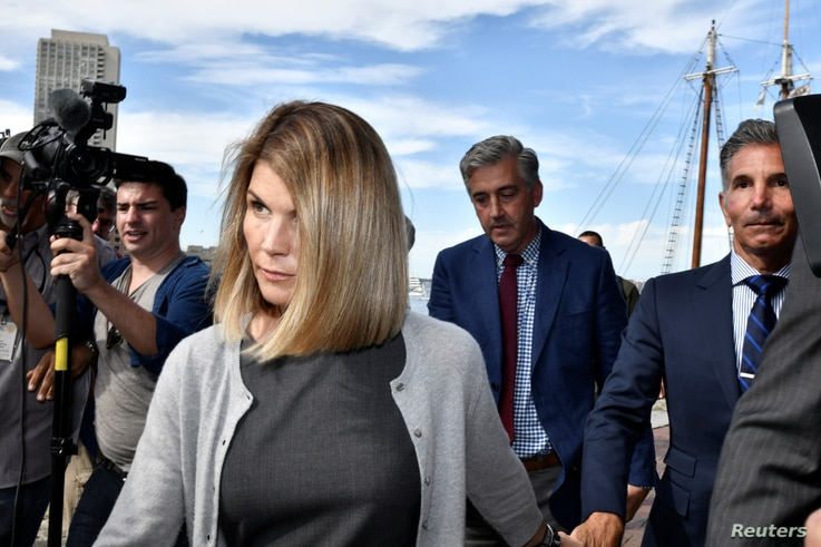 FILE - Actress Lori Loughlin, and her husband, fashion designer Mossimo Giannulli leave the federal courthouse after a hearing on charges in a nationwide college admissions cheating scheme in Boston, Massachusetts, Aug. 27, 2019.