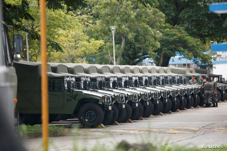 FILE - Troops are seen by a row of over a dozen army jeeps at the Shek Kong military base of People's Liberation Army in New Territories, Hong Kong, China, Aug. 29, 2019.