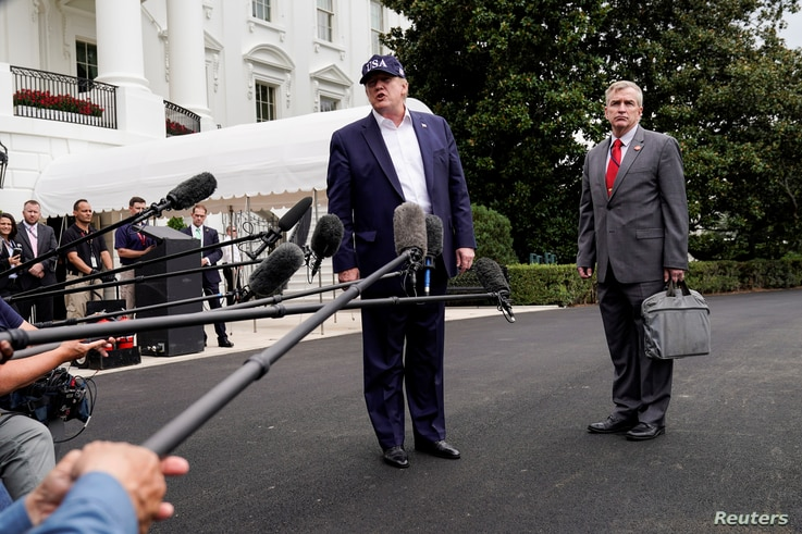 FILE - U.S. President Donald Trump speaks to the media about Hurricane Dorian with Rear Admiral Peter J. Brown, Assistant Commandant for Response Policy, as he returns from Camp David to the White House, Sept. 1, 2019.