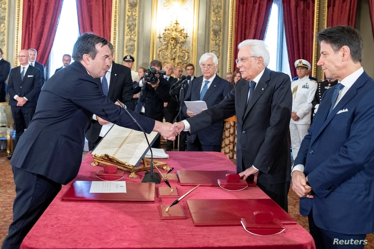 Vincenzo Amendola, left, shakes hands with Italian President Sergio Mattarella as he is sworn in as Italy's European affairs minister during a ceremony in Rome, Sept. 5, 2019.