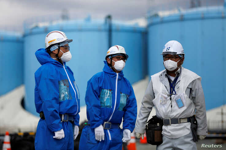 FILE - Workers are seen in front of storage tanks for radioactive water at Tokyo Electric Power Co's tsunami-crippled Fukushima Daiichi nuclear power plant in Okuma town, Fukushima prefecture, Japan, Feb. 18, 2019.