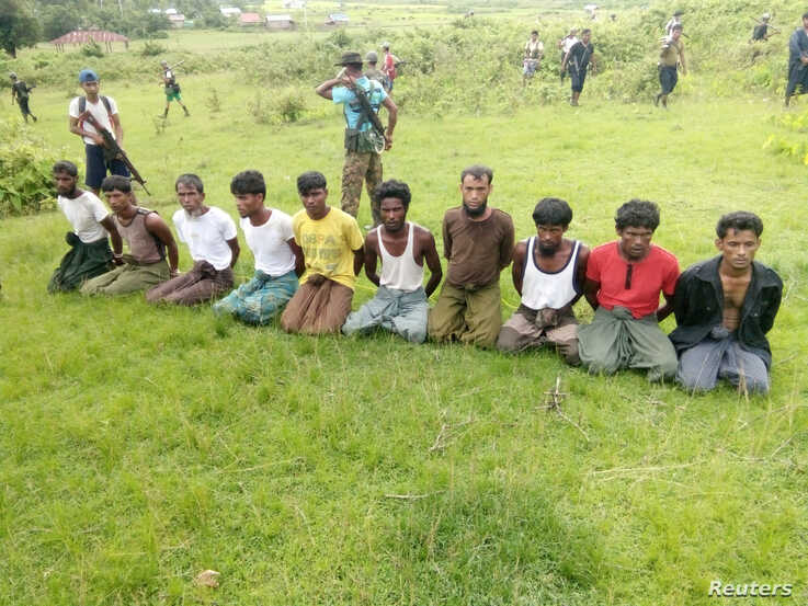 FILE - Ten Rohingya men with their hands bound kneel as members of the Myanmar security forces stand guard in Inn Din village of Rakhine State, Myanmar, Sept. 2, 2017.