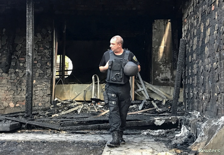 A law enforcement officer walks at the site of a burnt house, which is reportedly owned by former Governor of the Ukrainian Central Bank Valeria Gontareva, in Kyiv, Ukraine, Sept. 17, 2019.