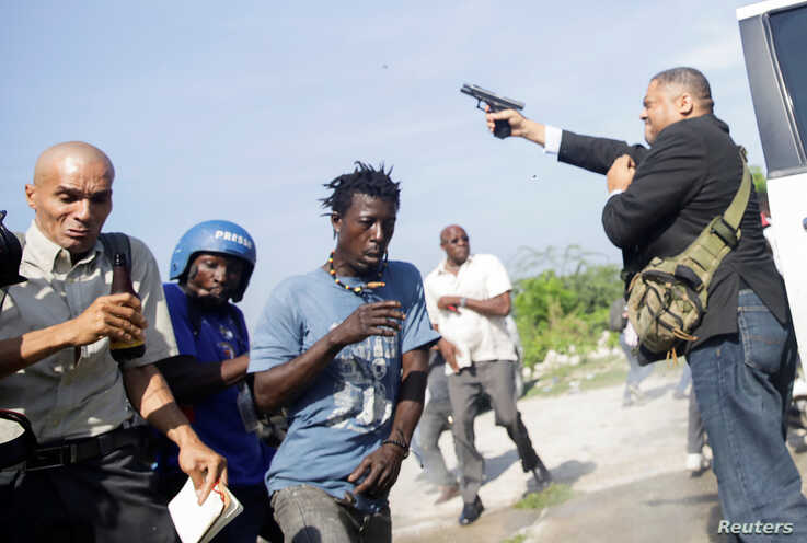 People run as Haiti's Senator Jean Marie Ralph Fethiere holds a gun in Port-au-Prince, Haiti September 23, 2019.
