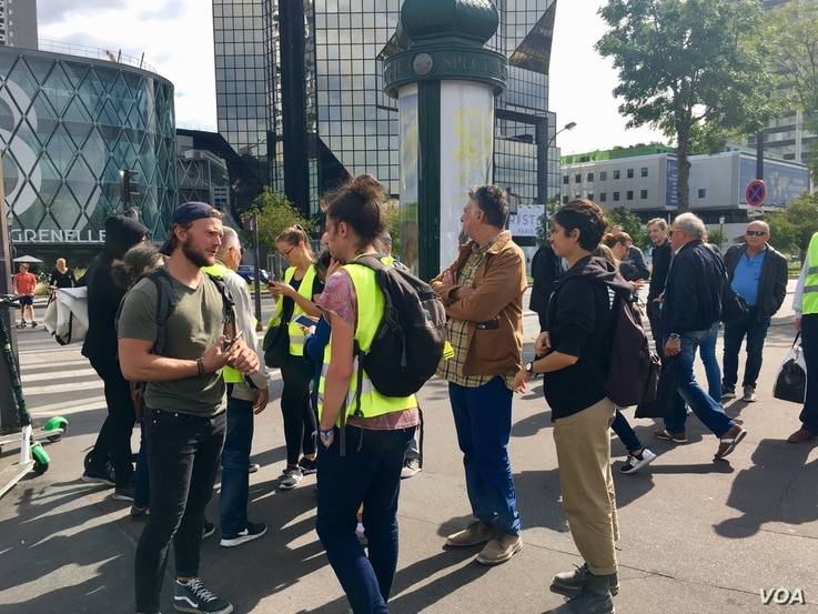 Yellow vest protesters wait near the Seine River for other members to join them, Sept. 7, 2019. (L. Bryant/VOA)