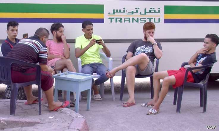 Young men are seen at a bus stop cafe in Tunis. Unemployment reaches 30 percent in some parts of Tunisia. (L. Bryant/VOA)