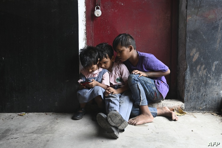 Children play on a cell phone at a market in New Delhi, India.