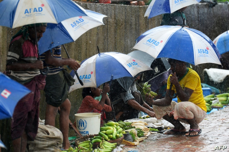 Rohingya refugees hide under umprellas during rainfall at Kutupalong refugee camp in Ukhia, Cox's Bazar, Bangladesh, Sept. 12, 2019.