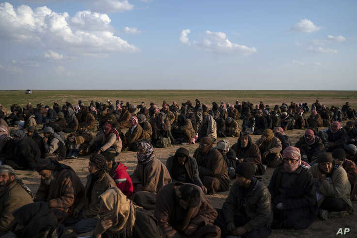 FILE - Men wait to be screened by U.S.-backed Syrian Democratic Forces (SDF) fighters after being evacuated out of the last territory held by Islamic State militants, near Baghuz, eastern Syria, Feb. 22, 2019.