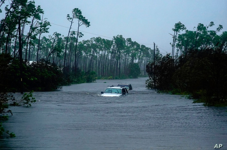 Cars sit submerged in water from Hurricane Dorian in Freeport, Grand Bahama.