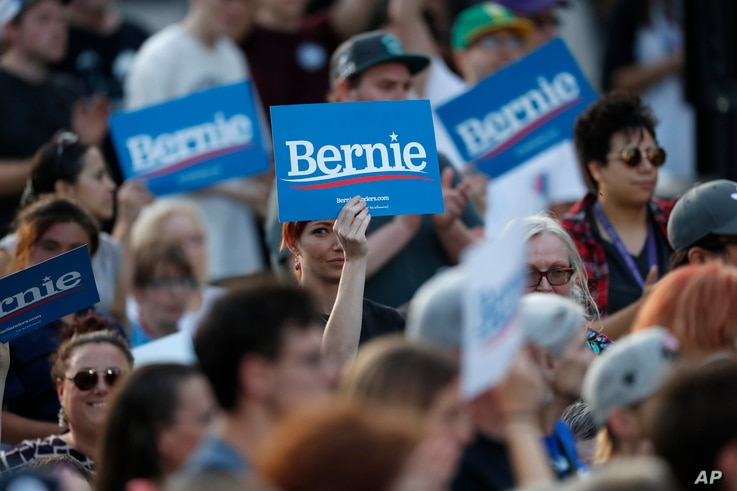 FILE - Supporters wave signs in support of Democratic presidential candidate Senator Bernie Sanders, as he speaks during a campaign rally in Denver, Colorado, Sept. 9, 2019.