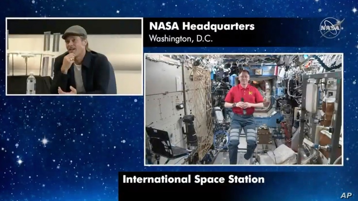 """In this image taken from NASA video actor Brad Pitt, left, star of the new space movie """"Ad Astra,"""" speaks from NASA headquarters in Washington, to astronaut Nick Hague abroad the International Space Station, Sept. 16, 2019."""
