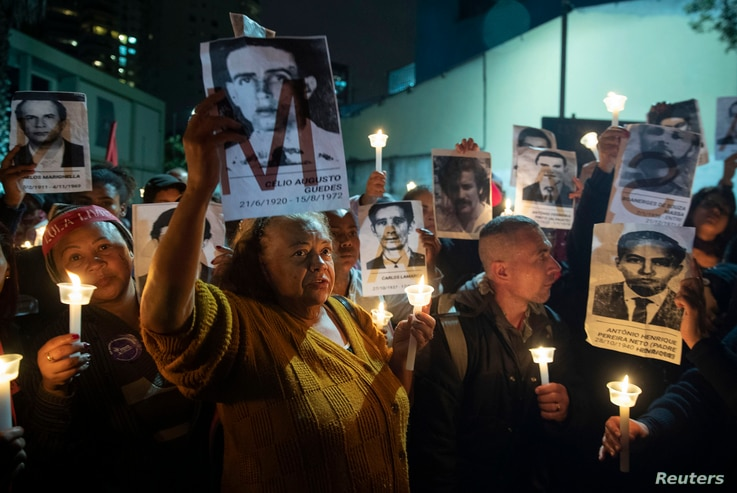 Demonstrators hold photos of people killed during Brazil's dictatorship outside a Sao Paulo police station that used to be a torture center, as they protest the removal of members of a commission investigating disappearances, Aug. 5, 2019.