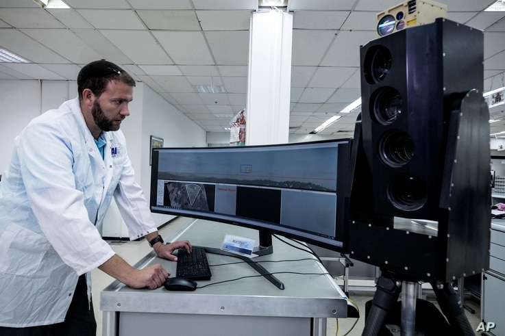 FILE - Ariel Gomez, a systems engineer works on the Popstar system that can track and identify flying objects day or night without being detected, at Israel Aerospace Industries, in the town of Yehud near Tel Aviv, Sept. 9, 2019.