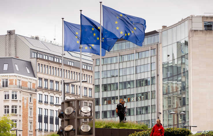 European Union flags flap in the wind as two gardeners work on the outside of EU headquarters in Brussels, Sept. 11, 2019