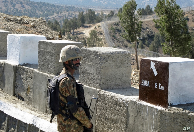 FILE - A Pakistani soldier stands guard at a border fence between Pakistan and Afghanistan, at Angore Adda, Pakistan, Oct. 18, 2017.