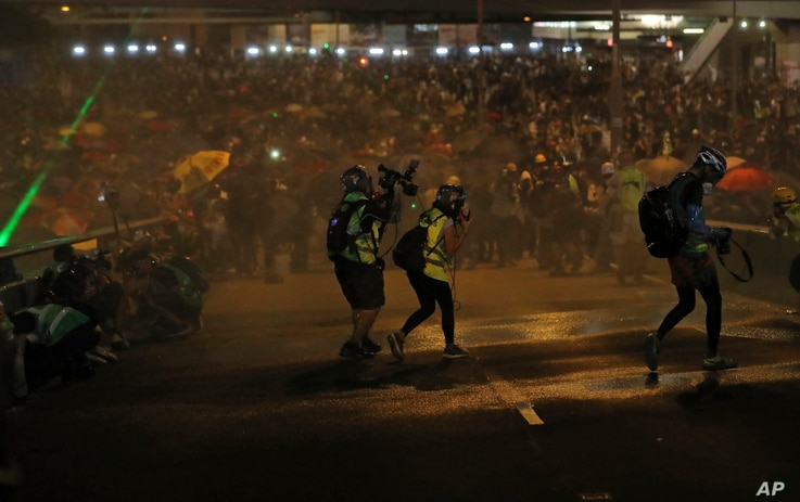 Photographers take cover as police fire water cannon on protesters in Hong Kong, Sept. 28, 2019.