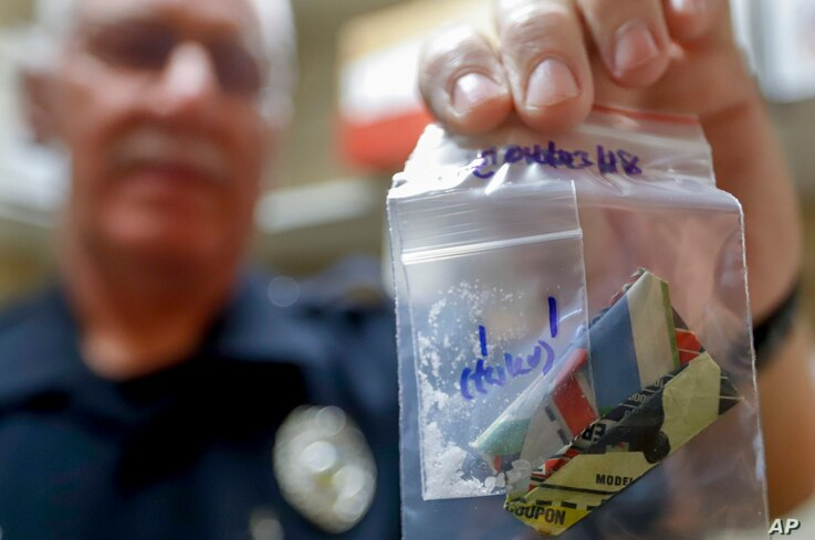 Narcotics detective Will Pfeiffer displays an evidence bag containing methamphetamine before it is destroyed in Barberton, Ohio, Sept. 11, 2019.