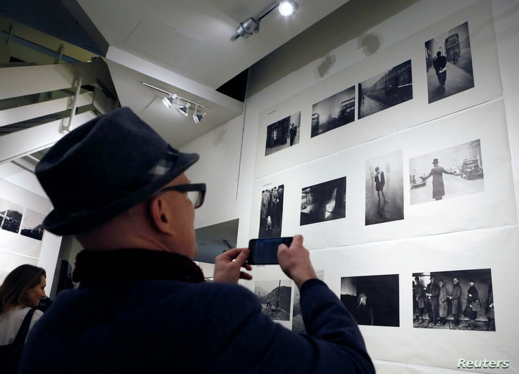 "A man takes a cell phone photograph of a wall full of photographs by Robert Frank at the opening of the exhibition featuring his work, ""Robert Frank: Books and Films, 1947–2016,"" at New York University's Tisch School of the Arts, Jan. 28, 2016."