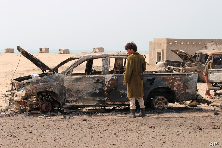 A Yemeni southern separatist fighter inspects the wreckage of government forces vehicles destroyed by UAE airstrikes near Aden, Aug. 30, 2019.