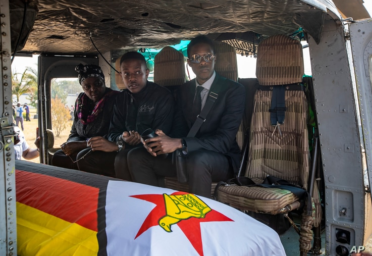 Former president Robert Mugabe's two sons Chatunga Mugabe, center, and Robert Mugabe Junior, right, accompany his casket in an air force helicopter for transport to a stadium where it will lie in state, in the capital Harare, Zimbabwe, Sept. 13, 2019.