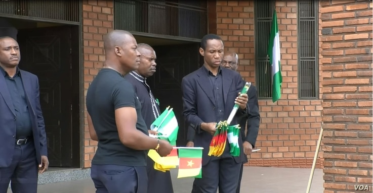 Men hand out flags to people praying for peace in Cameroon's restive English-speaking regions, at Saint Joseph's Anglophone Parish in Cameroon's capital, Yaounde, Sept. 6, 2019. (M.Kindzeka/VOA)