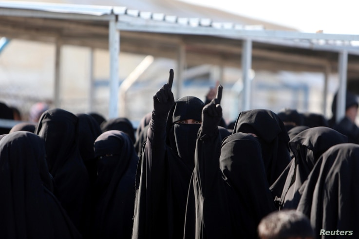 FILE - Women gesture as they stand together at the al-Hol displacement camp in Hasaka governorate, Syria, April 2, 2019.