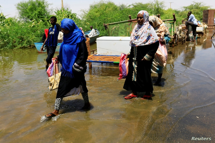 People carry their belongings as they wade through flood waters near the River Nile, on the outskirts of Khartoum, Sudan, Sept. 2, 2019.