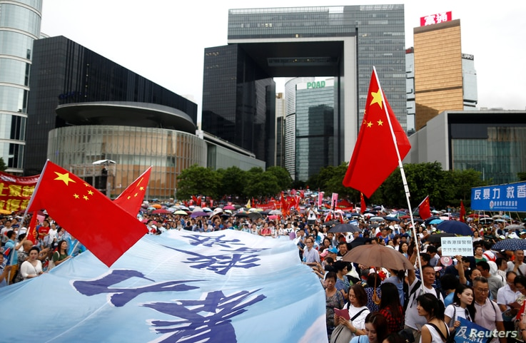 "People wave Chinese flags during a pro-China ""Safeguard Hong Kong"" rally at Tamar Park to voice support for the police and call for an end to violence, in Hong Kong, Aug. 17, 2019."