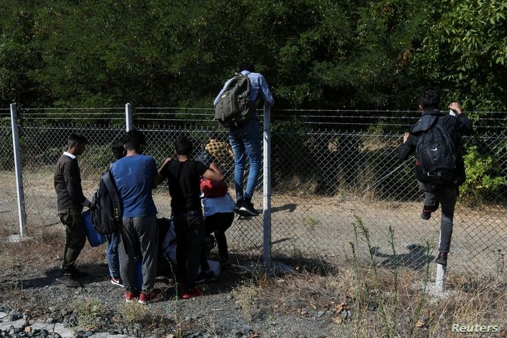 FILE - Migrants jump a fence after reaching the Greek-North Macedonian border on a freight train, trying to cross without documents, near the village of Idomeni, Greece, Aug. 24, 2019.