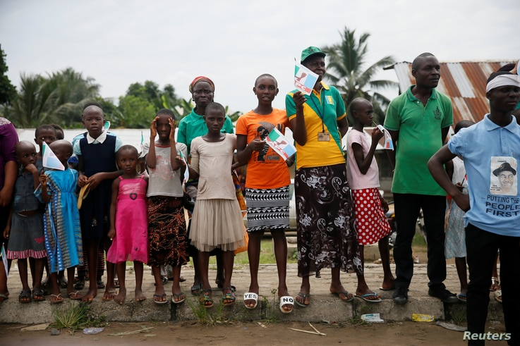 People hold flags of the ruling APC party as they stand along a road in Bodo, Nigeria, to show support for the start of the government's exercise to clean up pollution in Ogoni land, Nigeria, June 2, 2016.