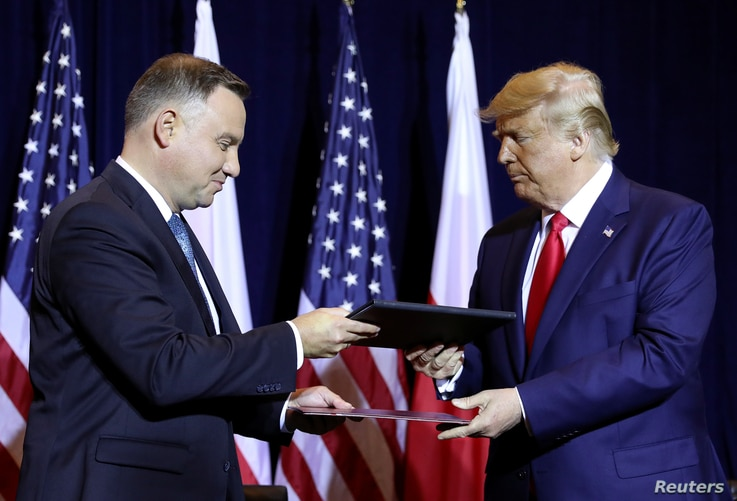 "U.S. President Donald Trump and Poland's President Andrzej Duda exchange documents after signing a ""joint declaration enhancing defense cooperation"" prior to their bilateral meeting on the sidelines of the annual U.N. General Assembly in New York, Sept. 23, 2019."