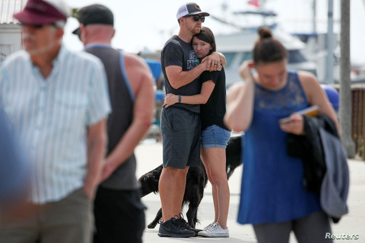 Two people hug as they they look over a makeshift memorial near Truth Aquatics as the search continues for those missing in a pre-dawn fire that sank a commercial diving boat near Santa Barbara, California, Sept. 3, 2019.