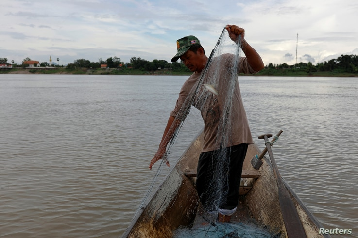 A fisherman pulls a fishing net from his boat in the Mekong River in Nakhon Phanom, Thailand, July 24, 2019.