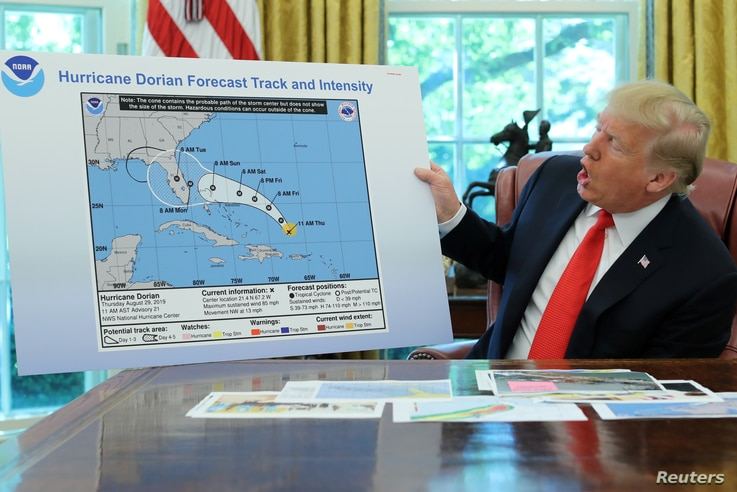 U.S. President Donald Trump holds a projected track of Hurricane Dorian map that appears to have been extended to Florida and parts of Alabama during a meeting on the hurricane in the Oval Office of the White House in Washington, Sept. 4, 2019.