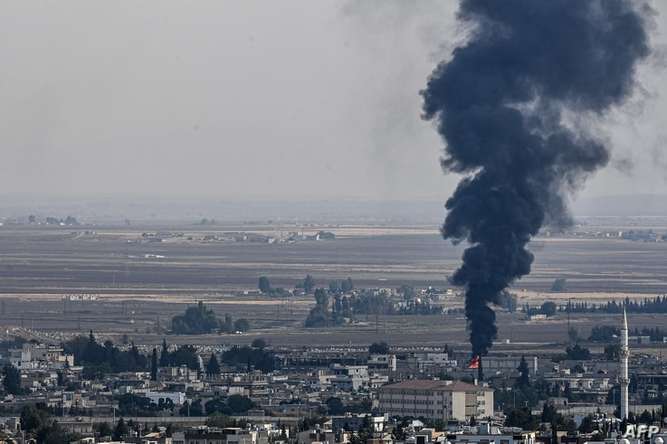 This picture taken on October 18, 2019 from the Turkish side of the border at Ceylanpinar district in Sanliurfa shows fire and…