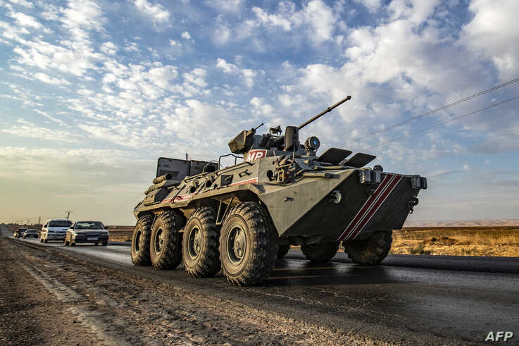 A Russian military police armoured personnel carrier (APC) drives along a road in the countryside near the northeastern Syrian…