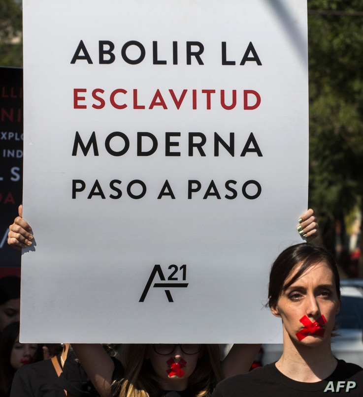 """A woman holds a poster reading """"Abolish modern slavery step by step"""" as she joins hundreds wearing black shirts and bearing red…"""