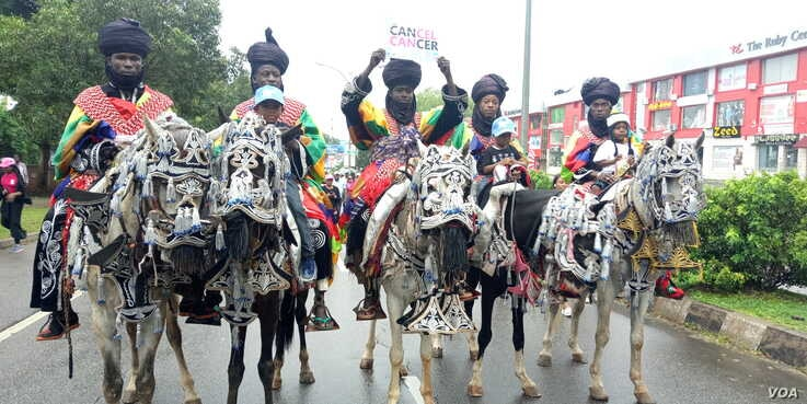 "Horsemen from Northern Nigeria hold ""cancel cancer"" signs during a cancer awareness walk in Abuja, Nigeria, Oct. 26, 2019. (Timothy Obiezu/VOA)"