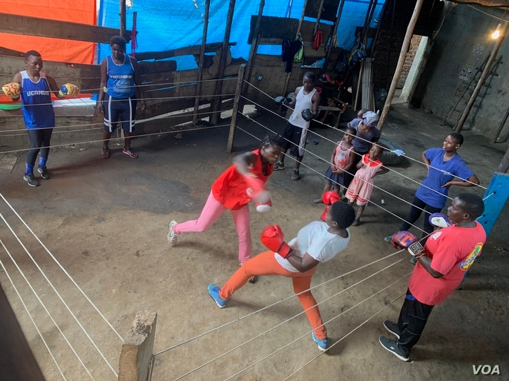 Two women in a boxing training session in Katanga Slum as Hellen Baleke outside the ring looks on.