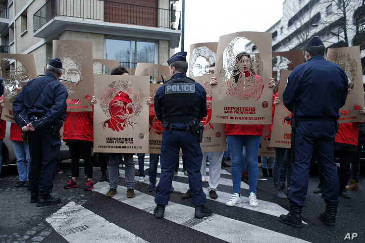 FILE - Members of Reporters Without Borders (RSF) hold stencils representing portraits of imprisoned Turkish journalists, during a...