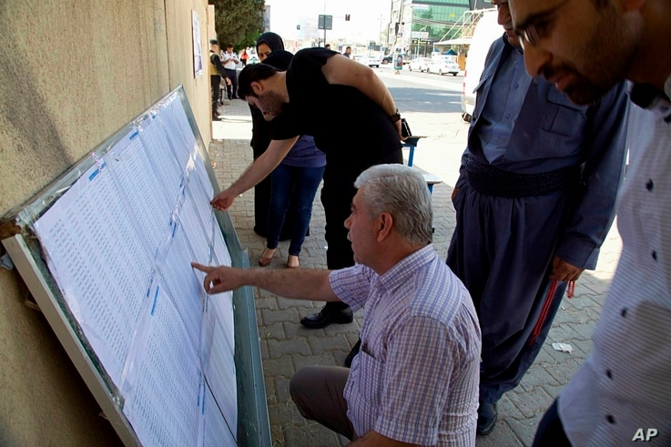 Iraqi Kurds search for their names on polling center lists during parliamentary elections in Irbil, Iraq, Sunday, Sept. 30,…