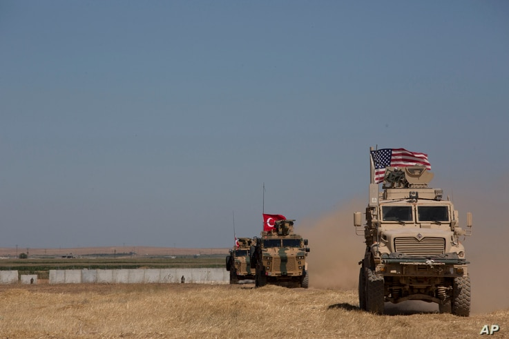 """Turkish and American forces conduct their first joint ground patrol in the so-called """"safe zone"""" on the Syrian side of the…"""