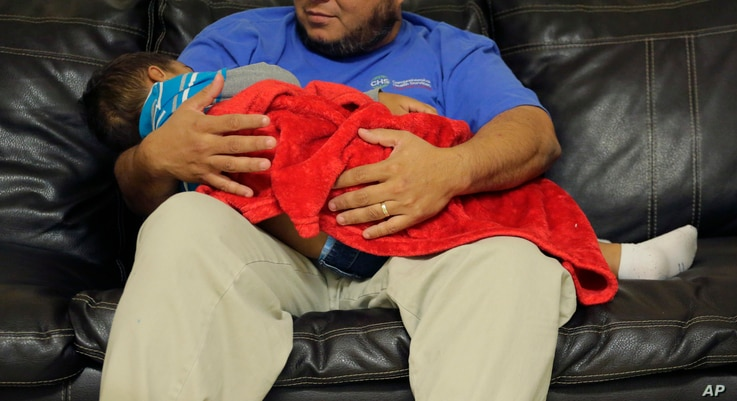 """A migrant toddler is cradled by a Comprehensive Health Services, Inc. caregiver at a """"tender-age"""" facility for babies, children and teens, in Texas' Rio Grande Valley, Aug. 29, 2019, in San Benito, Texas."""