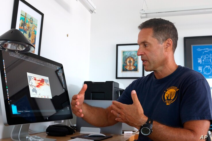 Ecologist Greg Asner, the director of Arizona State University's Center for Global Discovery and Conservation Science, reviews ocean temperature data at his lab on the west coast of the Big Island near Captain Cook, Hawaii, Sept. 13, 2019.