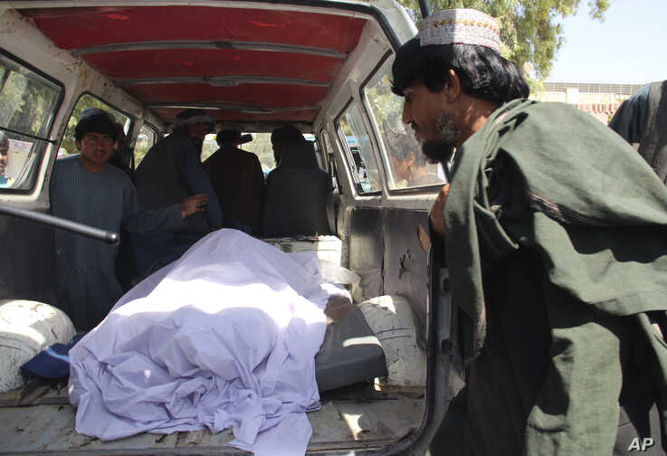Afghans transport the body of a woman who was killed during a raid conducted by Afghan special forces, in the southern Helmand…