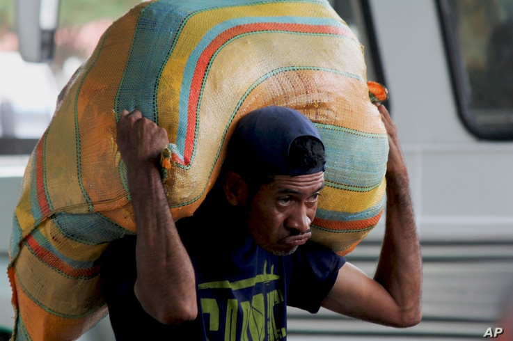 "A man carries a load on his back as he works as a ""lomo taxista,"" or taxi of the lower back, outside a bus terminal in San Antonio, Venezuela, Sept. 19, 2019."