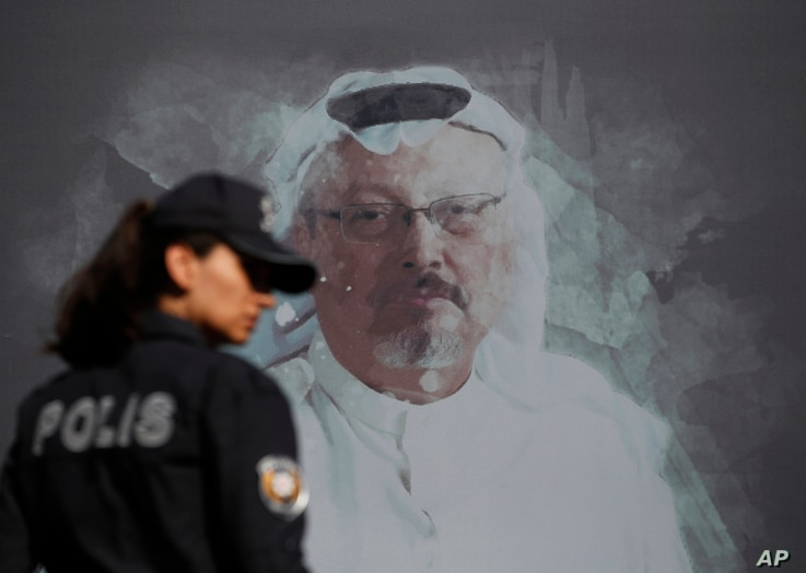 A Turkish police officer walks past a picture of slain Saudi journalist Jamal Khashoggi prior to a ceremony, near the Saudi...