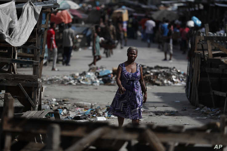 People walk through a market street, where wooden stands were used by protesters to barricade the road, in central Port-au-Prince, Haiti, Oct. 2, 2019.